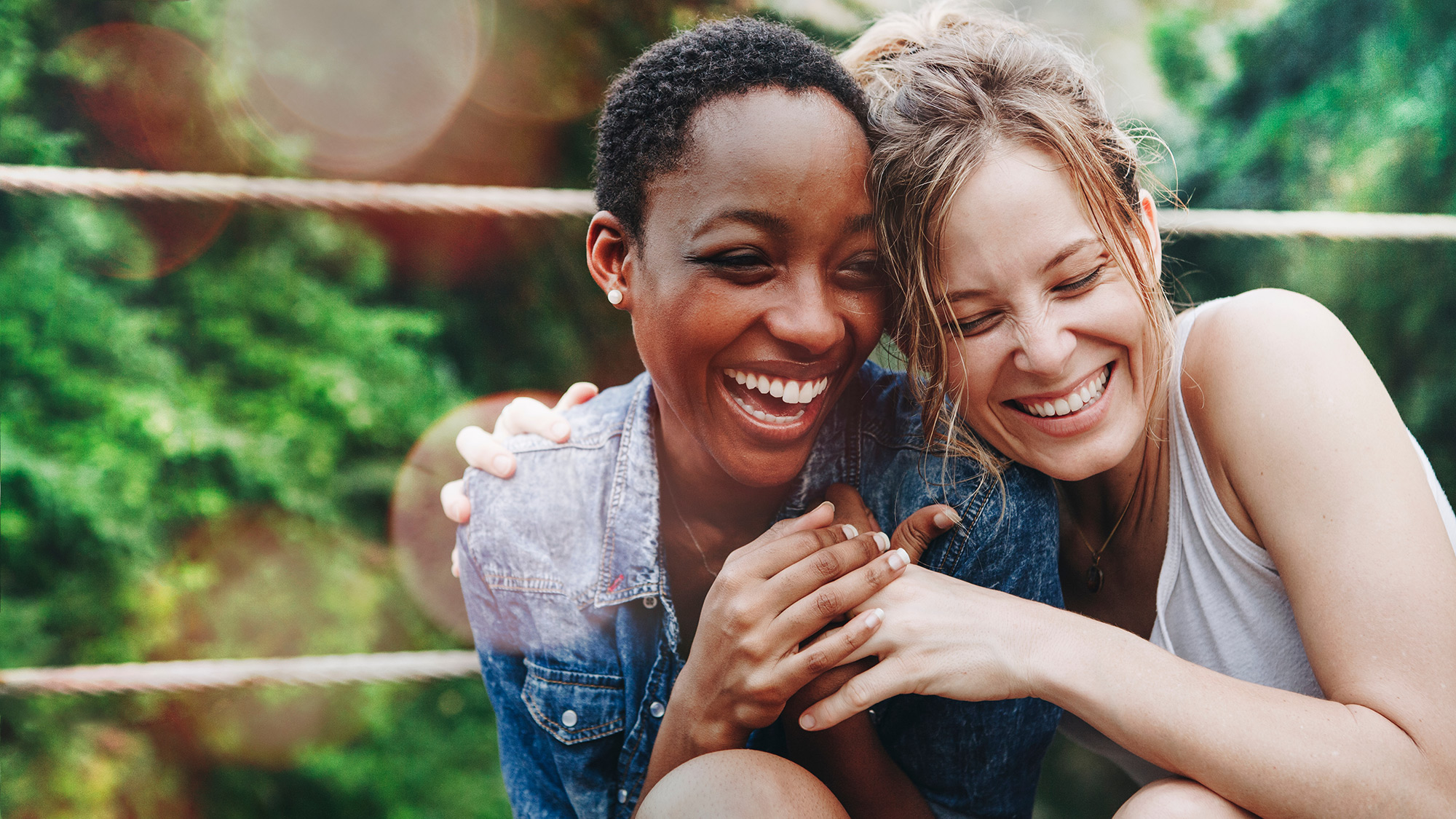 Two women friends happy, laughing and hugging